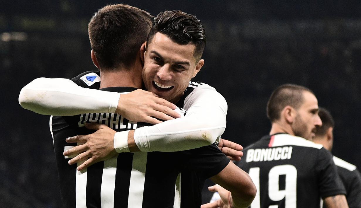 Striker Juventus, Cristiano Ronaldo, merayakan gol yang dicetak Paulo Dybala ke gawang Inter Milan pada laga Serie A di Stadion San Siro, Milan, Minggu (6/10). Inter kalah 1-2 dari Juventus. (AFP/Marco Bertorello)