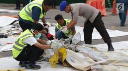 Petugas mengecek dan mengidentifikasi barang property pesawat Lion Air PK-LQP JT 610 di Pelabuhan JICT 2, Jakarta, Senin (5/11). Sejumlah barang ditemukan petugas gabungan dalam operasi pencarian. (Liputan6.com/Helmi Fithriansyah)
