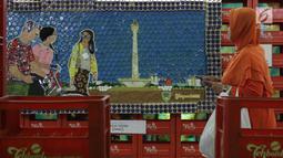 Pengunjung melihat-lihat karya seni instalasi dari bahan bekas pakai yang dipamerkan di terowongan Jalan Kendal-Blora, Jakarta, Selasa (20/8/2019). Rangkaian seni instalasi ini bertema tentang kota Jakarta dan transportasi kereta berlangsung hingga 25 Agustus mendatang. (Liputan6.com/Helmi Fithrians