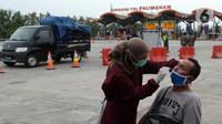 Petugas medis melakukan tes COVID-19 terhadap seorang pria di Gerbang Tol Palimanan, Jakarta, Jumat, (7/5/2021). Gerbang Tol Palimanan sepi karena adanya kebijakan larangan mudik Lebaran pada tanggal 6-17 Mei 2021 untuk memutus penyebaran COVID-19. (merdeka.com/Imam Buhori)