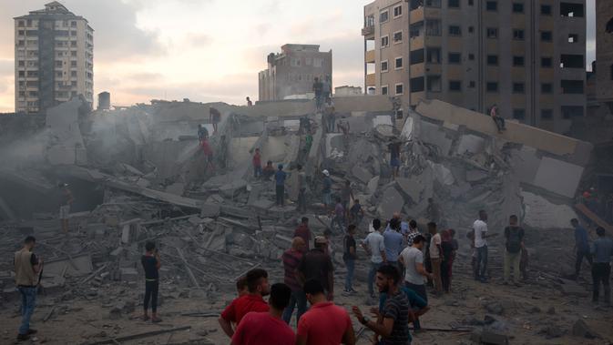 Warga melihat puing-puing bangunan yang hancur akibat serangan udara Israel di Kota Gaza, Palestina, (9/8). Tentara Israel kembali membombardir Gaza sebagai aksi balasan terhadap serangan militan Hamas. (AP Photo/Khalil Hamra)