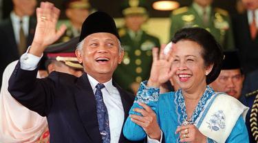 Presiden BJ Habibie didampingi istrinya Ainun Habibie melambaikan tangan kepada wartawan usai menghadiri upacara pelantikan anggota baru parlemen di luar Gedung Parlemen, Jakarta, 1 Oktober 1999. Habibie meninggal pada Rabu, 11 September 2019 pukul 18.05 WIB. (AFP Photo/STR)