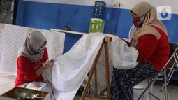 Perajin batik sedang menyelesaikan proses pembuatan batik tulis di Sanggar Batik Kembang Mayang, Larangan, Tangerang, Banten, Minggu (19/7/2020). Kain batik tulis dengan motif khas Tangerang ini dijual mulai dari Rp 450.000. (Liputan6.com/Angga Yuniar)