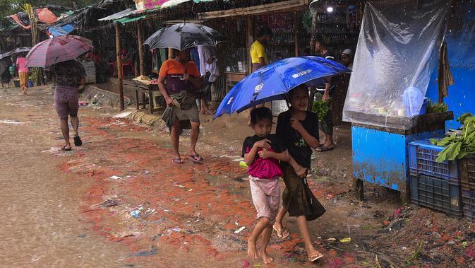 Dua anak pengungsi Rohingya berjalan menggunakan payung saat hujan di kamp pengungsi Kutupalong, Ukhia (12/9/2019). Kamp ini didirikan secara tidak resmi pada tahun 1991, setelah ribuan orang Rohingya melarikan diri dari Operasi Pyi Thaya yang dilancarkan militer Burma. (AFP Photo/Munir Uz Zaman)