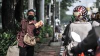 Pedagang asongan menjajakan dagangannya di lampu merah kawasan Manggarai, Jakarta, Minggu (18/10/2020). Institute for Development of Economics and Finance (Indef) memproyeksikan jumlah penduduk miskin naik 1,63 juta jiwa atau 0,56 persen selama masa pandemi Covid-19. (merdeka.com/Iqbal S. Nugroho)