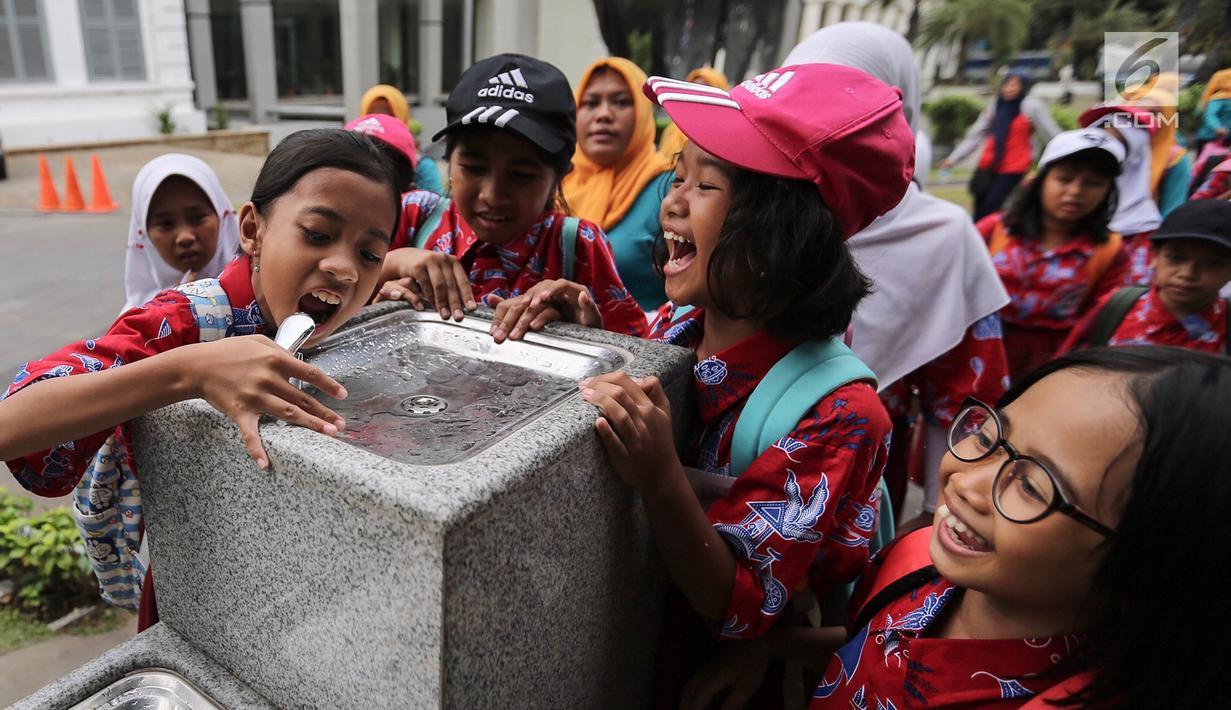 Anak-anak sekolah berebut air minum di fasilitas air siap minum (Drinking Fountain) di Museum Nasional, Jakarta, Kamis (8/11). Pembangunan drinking fountain ini untuk menyediakan air siap minum yang higienis bagi masyarakat. (Liputan6.com/Fery Pradolo)