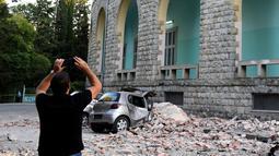 Seorang pria mengabadikan gedung yang runtuh sai gempa berkekuatan 5,6 magnitudo mengguncang Tirana, Albania (21/9/2019). Efek dari gempa bumi tersebut mengakibatkan puluhan bangunan hancur serta memicu pemadaman listrik di ibu kota Tirana. (AFP Photo/Gent Shkullaku)