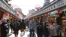 Pejalan kaki melintas di bawah dekorasi shio babi tanah yang mengarah ke kuil Buddha Asakusa Sensoji di Tokyo, Jepang, Kamis (27/12). Tahun 2019 dipercaya menjadi waktu yang tepat untuk menghasilkan uang dan berinvestasi. (AP Photo/Koji Sasahara)