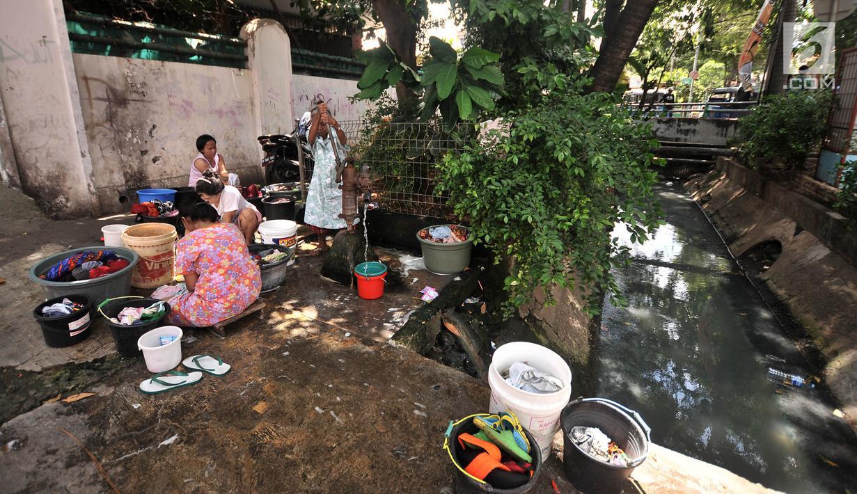 Warga mencuci pakaian di pinggir jalan kawasan Kramat Pulo, Senen, Jakarta, Kamis (27/12). Minimnya tempat MCK pribadi memaksa warga di Kramat Pulo menggunakan lahan di pinggir jalan untuk mencuci pakaian dan piring mereka. (Merdeka.com/Iqbal S. Nugroho)