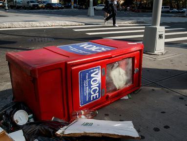 Sebuah kotak surat kabar Village Voice tergeletak di samping tempat sampah di Manhattan, AS (22/8). Village Voice  adalah surat kabar mingguan tertua dan paling terkenal di AS. (Drew Angerer/Getty Images/AFP)
