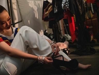 Seorang model menyesuaikan sepatu high heelsnya di belakang panggung sebelum memamerkan koleksi oleh Zhang Kejia selama China Fashion Week di Beijing (26/3). (AFP Photo/Nicolas Asfouri)
