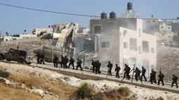 Pasukan keamanan Israel berjaga di tengah penghancuran bangunan Palestina dengan alat berat di Tepi Barat (22/7/2019). Palestina menuduh Israel menggunakan keamanan sebagai dalih untuk mengusir mereka dari Tepi Barat. (AFP Photo/Hazem Bader)