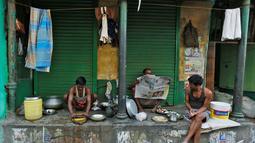 Sejumlah pekerja mempersiapkan makan pagi dan membaca koran di depan toko di Kolkata, India (26/5/2016). Kolkuta ialah ibu kota India antara 1833 sampai 1912  Terdapat Universitas Kolkata dan Museum India. (REUTERS/Rupak De Chowdhuri)