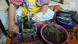 Pekerja memotong olahan kerupuk kulit pisang di  Industri rumahan kawasan Depok, Senin (4/3/2019). Kerupuk kulit pisang dijual Rp 10.000 per kantong dengan ukuran 100g yang di pasarkan ke wilayah Indonesia serta supermarket. (Liputan6.com/Herman Zakharia)