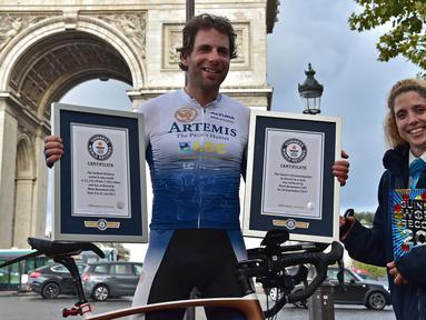 Pembalap sepeda Inggris, Mark Beaumont (34) berpose dengan sertifikat Guinness World Records setibanya di Arc de Triomphe, Paris, setelah menyelesaikan tur keliling dunia dalam waktu 78 hari, Senin (18/9). (CHRISTOPHE ARCHAMBAULT / AFP)