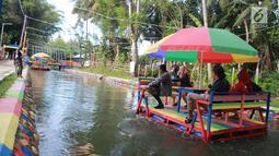 Wisatawan menaiki perahu apung di Wisata Air Toino, Desa Talulobutu, Kecamatan Tapa, Kabupaten Bone Bolango, Gorontalo, Sabtu (30/3). Kendati baru, tempat wisata buatan ini mulai diminati banyak wisatawan. (Liputan6.com/Arfandi Ibrahim)
