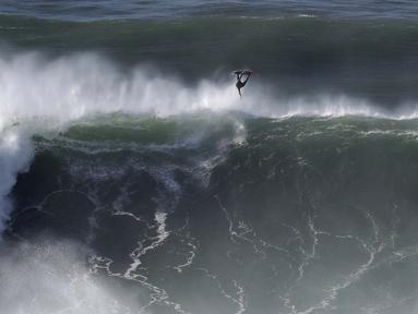 Seorang peselancar keluar dari ombak selama sesi selancar derek di Praia do Norte di Nazare, Portugal (29/10/2020). Gelombang besar, yang ditimbulkan oleh Badai Epsilon di Atlantik Utara, mencapai Portugis pantai barat menarik peselancar ombak besar ke Nazare. (AP Photo/Pedro Rocha)