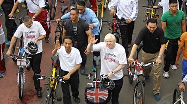Presiden Joko Widodo bersama Walikota London, Boris Johnson melambaikan tangan saat bersepeda bersama di kawasan Bundaran HI Jakarta, Minggu (30/11/2014). (Liputan6.com/Faizal Fanani)