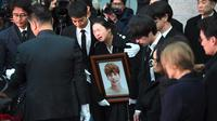 Sedangkan kakak dari Jonghyun tak kuasa menahan tangis. Ia terlihat memeluk foto mendiang adiknya. (JUNG Yeon-Je/AFP)