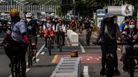 Warga bersepeda saat uji coba pembatas jalur sepeda permanen di kawasan Sudirman, Jakarta, Minggu (28/2/2021). Dalam uji coba tersebut terlihat masih banyak pesepeda yang melintas di luar jalur khusus yang telah disediakan. (Liputan6.com/Johan Tallo)