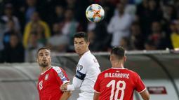 Striker Portugal, Cristiano Ronaldo, duel udara dengan bek Serbia, Nikola Maksimovic, pada laga Kualifikasi Piala Eropa 2020 di Belgrade, Sabtu (7/9). Serbia kalah 2-4 dari Portugal. (AFP/Pedja Milosavljevic)
