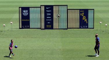 Pemain baru Barcelona, Arturo Vidal dan putranya Alonso Vidal menunjukkan skill bermain bola selama presentasi dirinya di stadion Camp Nou, Spanyol, (6/8). Vidal resmi diboyong Barcelona dengan kontrak selama tiga tahun. (AP Photo/Manu Fernandez)