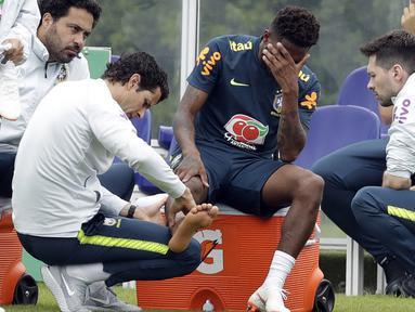 Pemain Brasil, Fred menahan sakit saat diperiksa dokter tim di lapangan latihan Tottenham Hotspur football club, Inggris, (7/6/2018). Fred mengalami masalah di engkel kaki. (AP/Matt Dunham)