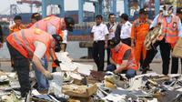 Petugas KNKT mencari dan memisahkan serpihan pesawat Lion Air JT 610 dari tumpukan barang temuan di Pelabuhan JICT 2, Jakarta, Kamis (1/11). Sebelumnya, pesawat Lion Air JT-610 jatuh diperairan utara Kerawang. (Liputan6.com/Helmi Fithriansyah)
