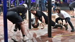 """Para peserta mengikuti kompetisi final CrossFit """"Game of Heroes"""" di Kiev, Ukraina (24/12). CrossFit sendiri adalah pola latihan yang mengabungkan olahraga kardiovaskuler dengan angkat beban ke dalam format serupa latihan sirkuit. (AFP/Sergei Supinsky)"""