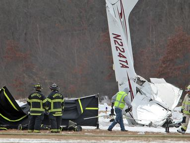 Tim penyelamat bekerja di lokasi kecelakaan pesawat kecil di Bandara Kota Mansfield, Massachusetts, AS, Sabtu (23/2). Kecelakaan menewaskan dua orang. (Matthew J. Lee/The Boston Globe via AP)