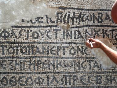 Arkeolog meneliti lantai mosaik berusia 1.500 tahun di Museum Rockefeller, Yerusalem, Rabu (23/8). Prasasti bertuliskan aksara dan bahasa Yunani kuno ditemukan selama pengerjaan pemasangan kabel komunikasi di Kota Tua Yerusalem. (AHMAD GHARABLI/AFP)