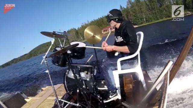 Seorang pria mampu unjuk gigi dengan memainkan drum pada perahu yang melaju di atas air.