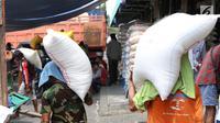 Seorang kuli angkut memanggul beras di Pasar Induk Cipinang, Jakarta, Senin (25/9). Pedagang beras Cipinang sudah menerapkan dan menyediakan beras medium dan beras premium sesuai harga eceran tertinggi (HET). (Liputan6.com/Angga Yuniar)