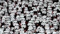 Suatu kerumunan penggemar Star Wars menonton sepak bola bersama dengan menggunakan kostum Storm Troopers. Demam Star Wars berlanjut.