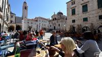 Wisatawan duduk di teras Stradun, jalan utama kota tua Dubrovnik pada 28 Maret 2019. Tahun lalu lebih dari 1,2 juta turis mengunjungi Dubrovnik, kota yang paling banyak dikunjungi di Kroasia. (Denis LOVROVIC / AFP)