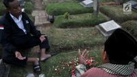 Seorang pria bernama Ma'ruf memimpin doa 'Talkin' untuk peziarah di Tempat Pemakaman Umum (TPU) Kemiri, Rawamangun, Jakarta, Selasa (15/5). (Merdeka.com/Iqbal S Nugroho)