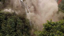 Momen saat peruntuhan sebuah jembatan gantung oleh para insinyur di Chirajara, Kolombia, Rabu (11/7). Sebelumnya, sebagian jembatan runtuh dan menewaskan sembilan pekerja saat pembangunannya pada Januari lalu. (AP Photo/Fernando Vergara)