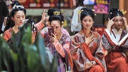 """Para peserta menunggu untuk ambil bagian dalam peragaan busana """"hanfu"""", pakaian tradisional khas China di kota Shenyang, China timur laut pada Minggu (15/9/2019). Hanfu sendiri sebenarnya adalah baju tradisional Cina yang digunakan etnis Han China. (Photo by STR / AFP)"""