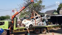 Petugas derek mengevakuasi bangkai mobil kecelakaan maut yang hancur tertindih badan truk muatan tanah di Karawaci, Tangerang, Kamis (1/8/2019). Lima orang penumpang minibus menjadi korban, empat diantaranya meninggal dan satu balita berhasil diselamatkan warga. (Liputan6.com/Pramita Tristiawati)