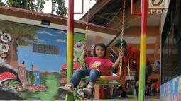 Seorang anak bermain ayunan di ruang publik terbuka ramah anak (RPTRA) Terminal Kampung Rambutan, Jakarta, Senin (27/5/2019). Menyambut arus mudik Lebaran 2019, RPTRA mini ini diharapkan bisa memberi hiburan bagi anak-anak yang hendak menunggu keberangkatan. (Liputan6.com/Herman Zakharia)