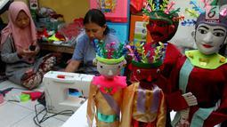 Perajin menyelesaikan pembuatan miniatur ondel-ondel di rumah produksi Kramat Jati, Jakarta, Senin (23/6/2019). Perajin dapat memproduksi 50  hingga 80 miniatur ondel-ondel dalam sebulan. (merdeka.com/Arie Basuki)
