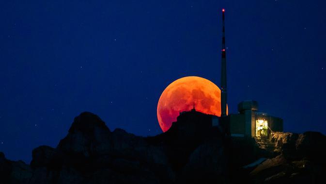 Bulan tampak berwarna merah darah saat terjadinya fenomena gerhana bulan total  di Luzern, Swiss, Jumat (27/7). Gerhana bulan yang terlama pada abad ini dapat disaksikan di seluruh dunia dengan mata telanjang. (Christian Merz/Keystone via AP)