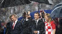 Presiden Rusia Vladimir Putin (kiri) bersama Presiden Prancis Emmanuel Macron (tengah) dan Presiden Kroasia Kolinda Grabar-Kitarovic berjalan dalam hujan usai laga final Piala Dunia 2018 di Stadion Luzhnik, Moskow, Rusia, Minggu (15/7). (Franck Fife/AFP)