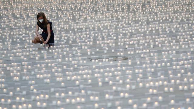 Seorang wanita menyalakan lilin untuk memperingati para korban pandemi virus corona COVD-19 di Kastil Praha, Praha, Republik Ceko, Senin (10/5/2021). Republik Ceko melonggarkan pembatasan terkait COVID-19 secara besar-besaran kendati hampir 30 ribu orang telah meninggal. (AP Photo/Petr David Josek)