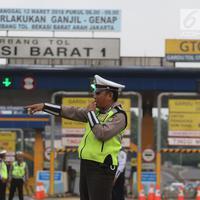 Polisi dan petugas Dishub berjaga di depan Gerbang Tol Bekasi Barat 1, Bekasi, Jabar, Senin (12/3). Ganjil genap ini merupakan kebijakan untuk mengurai kemacetan parah di tol Cikampek-Jakarta, khususnya ruas Bekasi-Jakarta. (Liputan6.com/Arya Manggala)