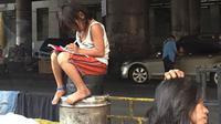 Potret seorang gadis kecil yang tengah mengerjakan pekerjaan rumah (PR) di sebuah jalanan di Filipina menyentuh hati orang-orang.