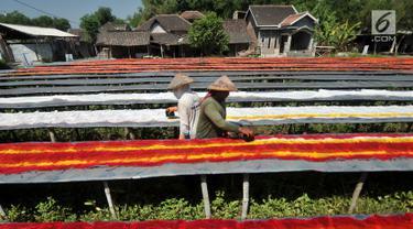 Pekerja mewarnai kain pantai di salah satu industri rumahan di Desa Krajan, Mojolaban, Sukoharjo, Jawa Tengah, Senin (10/6). Kecamatan Mojolaban merupakan sentra industri kain pantai yang perlahan terkenal berkat proses pembuatannya yang masih manual dan atraktif. (merdeka.com/Iqbal S. Nugroho)