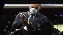 Seorang staf Ludogorets mengenakan masker sebelum turun dari bus menuju stadion San Siro, Milan, Italia (27/2/2020). Penggunaan masker dilakukan untuk mencegah Virus Korona yang telah menyebabkan 11 orang meninggal dunia di Italia. (Ludogorets FC via AP)