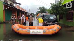 Karyawan PT. Askrindo secara simbolis memberikan bantuan perahu karet kepada warga korban banjir di Bekasi, Senin (22/02/2021). Bantuan perahu karet untuk proses evakuasi korban banjir diberikan di Pondok Timur Mas, Bekasi Selatan dan Perumnas III, Kota Bekasi. (Liputan6.com/Pool)