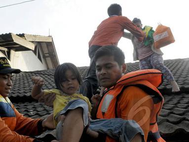Petugas Basarnas mengevakuasi warga ketika banjir melanda Perumahan Ciledug Indah 1, Tangerang, Selasa (10/2/2015). Banjir merendam ratusan rumah di kawasan tersebut dengan ketinggian mencapai 90 cm. (Liputan6.com/Andrian M Tunay)